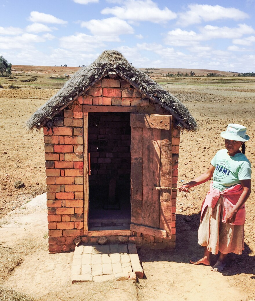 A woman in Madagascar stands by one of the new latrines in her village.