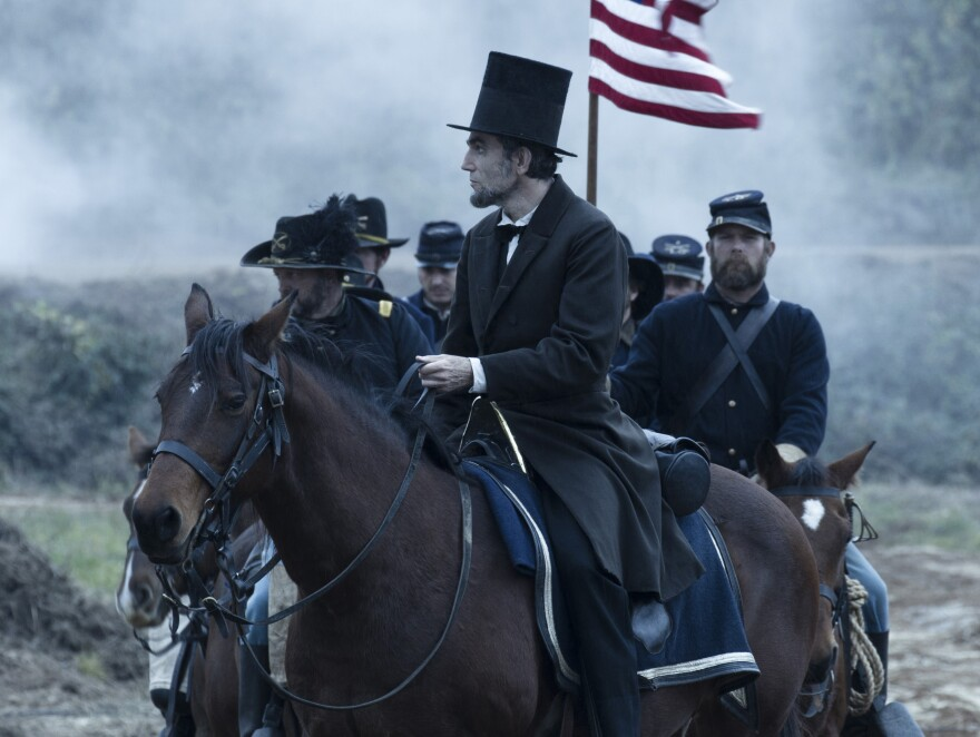 President Abraham Lincoln (Daniel Day-Lewis) looks across a battlefield in the aftermath of a terrible siege in <em>Lincoln</em>.