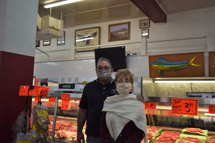 A man and woman stand in front of the meat counter of the family's grocery store.