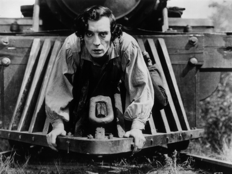 American actor Buster Keaton clinging to the front of a train in a still from the 1926 film, 'The General.'