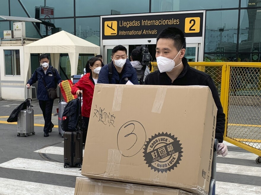 Members of a Chinese medical delegation arrive at the Lima airport with COVID vaccines for part of a clinical trial this fall. Peru hosted trials for several manufacturers in part to increase its chances of getting access to a successful inoculation.