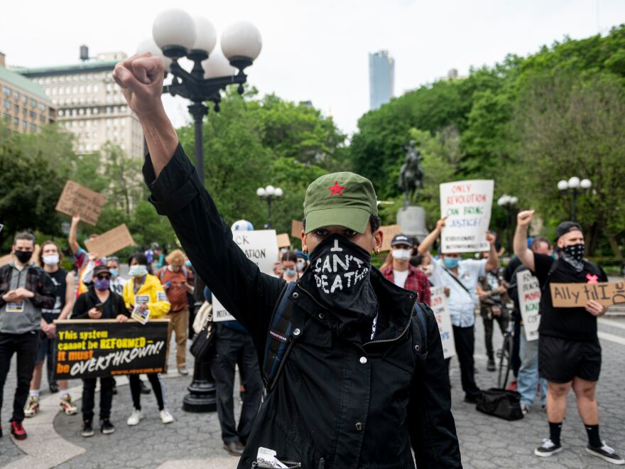 "A protester raises a fist during a ""Black Lives Matter"" demonstration Thursday in New York City — just one of a number of protests nationwide inspired by Floyd's death in Minneapolis."