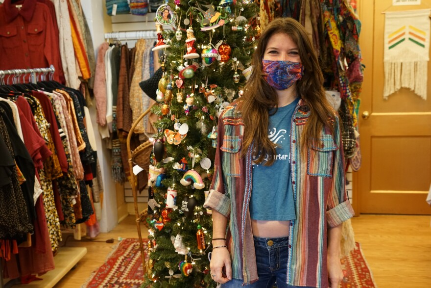 A young woman stands in a shop in front of a Christmas tree and racks of clothing.