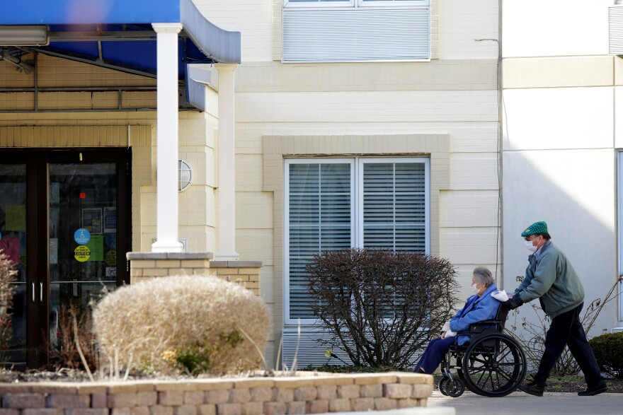 A woman is pushed in a wheelchair outside the Chateau Nursing and Rehabilitation Center, where health officials said a patient tested positive for COVID-19 in Willowbrook, Illinois.