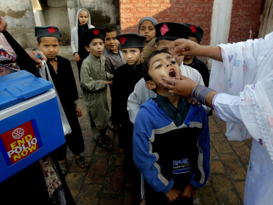 A Pakistani health worker gives a polio vaccine to students in Peshawar, Pakistan, in March. Polio remains endemic in Pakistan after the Taliban banned vaccinations, attacks targeted medical staffers and suspicions lingered about the inoculations.