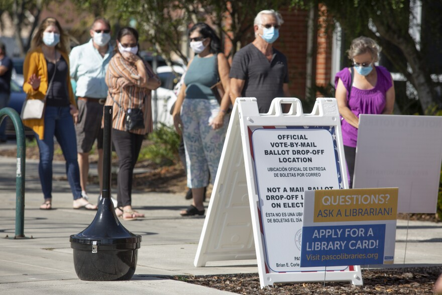 People wearing masks wait in line at a polling station. A sandwich board in front of them announces it is also a vote by mail ballot drop off location.