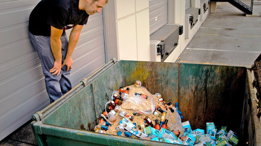 A scene from J<em>ust Eat It: A Food Waste Story</em>. Filmmaker Grant Baldwin checks out a dumpster of excess, but edible, food.