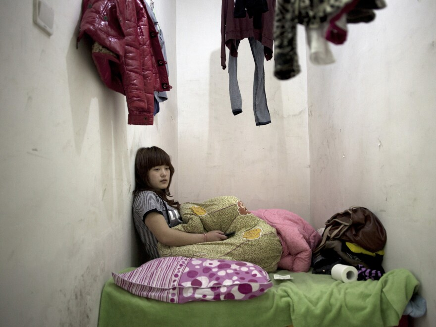 Twenty-one-year-old Liu Jing sits in her apartment two stories underground in Beijing, China. Her laundry hangs above her head because there's nowhere else to put her clothes.