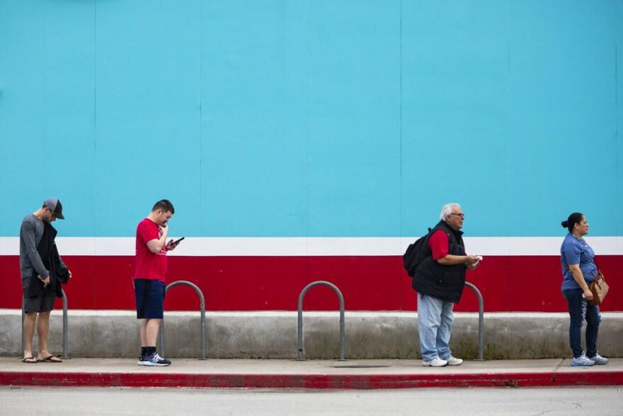 Una fila de clientes, separados unos de otros de acuerdo con las pautas de distanciamiento social, esperan para entrar en la tienda de comestibles HEB en el sur de Austin durante la pandemia de coronavirus.