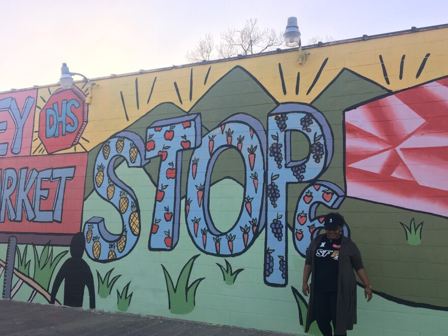"""Kendra Richardson, a young Black woman wearing a black shirt and green cardigan, stands in front of a colorful mural with the words """"Stop 6"""" painted on the wall."""