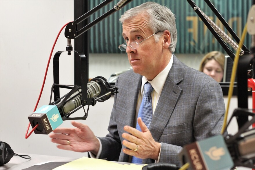 A white-haired man wearing glasses and a grey suit sits in front of a microphone in a radio studio.