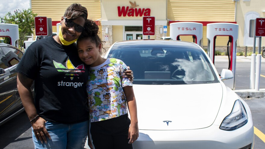 Tonya Riggles, left, and Maya Riggles, right, stand in front of an electric car