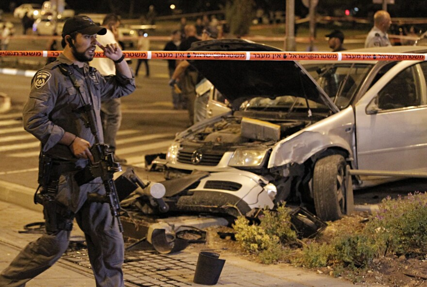 Israeli policemen secure the scene after Shaludi drove into a group of pedestrians in east Jerusalem on Oct. 22.