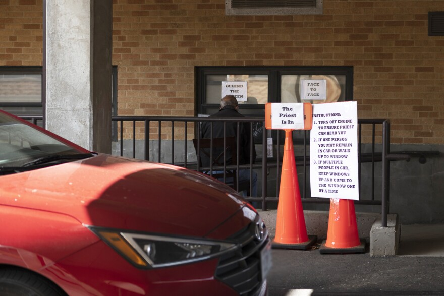 A congregant pulls up a chair to St. Francis of Assisi's drive-thru confessional on May 11, 2020. Father Anthony Yates and George Staley take turns manning the window three days a week, to provide spiritual solace for parishioners during the pandemic.