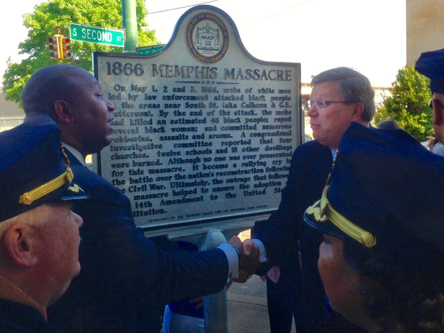 Memphis law enforcement looks on as the Rev. Keith Norman (left), president of the Memphis branch of the NAACP, shakes hands with Memphis Mayor Jim Strickland in front of the new historical marker.