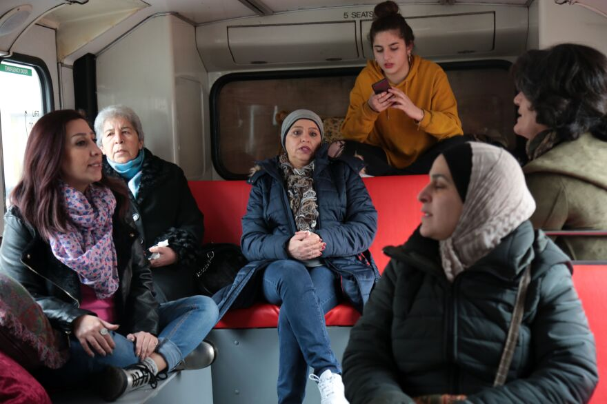 Activists with the group Families for Freedom, including Syrian lawyer Noura Ghazi (left), whose husband was executed in a Syrian prison, sit inside a bus after driving onto the Place de la République in Paris in January, during a campaign to demand freedom for those detained in Syria.