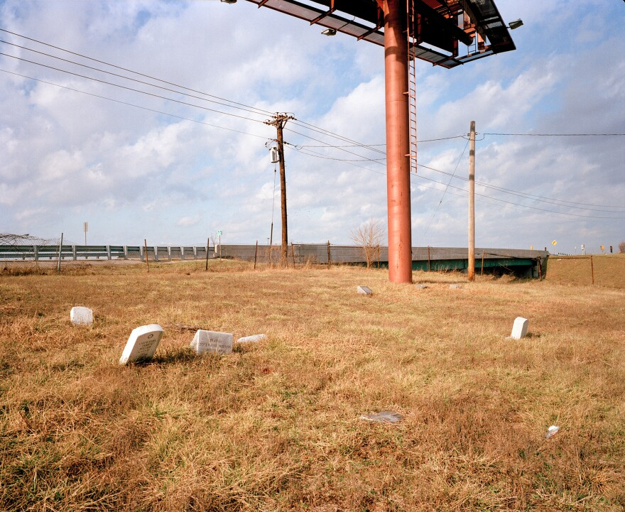 Several gravestones slouch toward the ground, overshadowed by a looming billboard with a highway in the background.