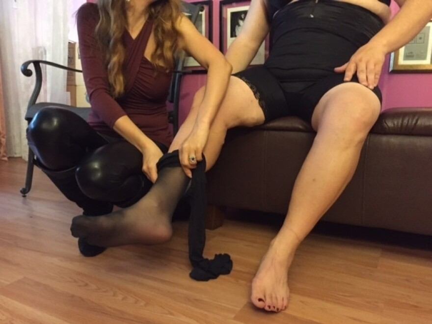 Miss Julia slipping stockings on Bianca.