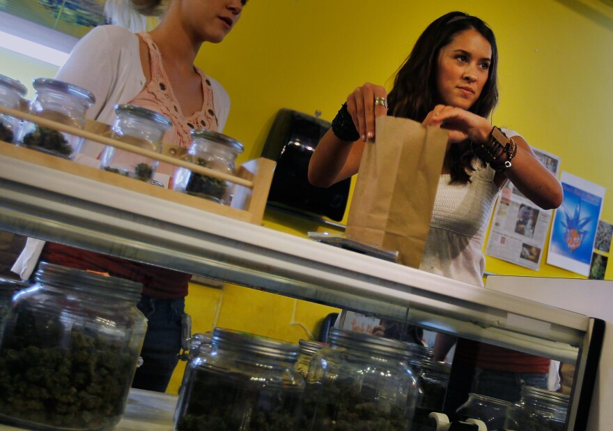 """Budtender"" Marissa Dodd bags up a marijuana sale at the Dr. Reefer marijuana dispensary across from the University of Colorado in Boulder, Colo."