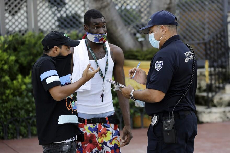 Code officer in uniform talks to men with masks