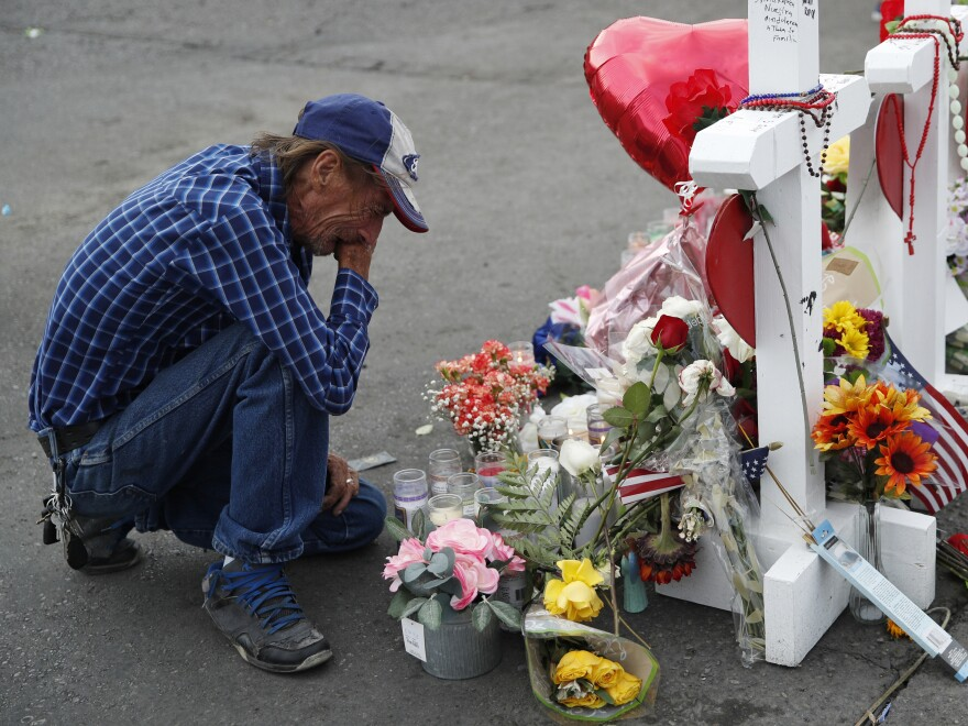 Antonio Basco cries beside a memorial near the scene of the recent mass shooting in El Paso, Texas. Basco, whose 63-year-old wife was among the victims, says he has no other family and welcomes anyone wanting to attend her funeral service.