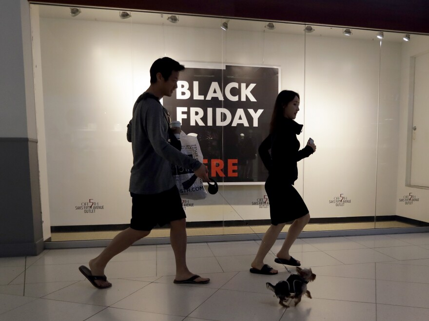 Shoppers walk past a Saks Fifth Avenue outlet store in Miami on Black Friday. Millennials have lower earnings, fewer assets and less wealth, a new Federal Reserve study says.