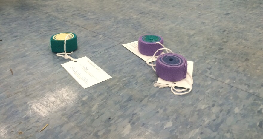 Completed scrolls, which are made by coiling and pinning recycled fabric belts, sit on the Coral Terrace art room floor.