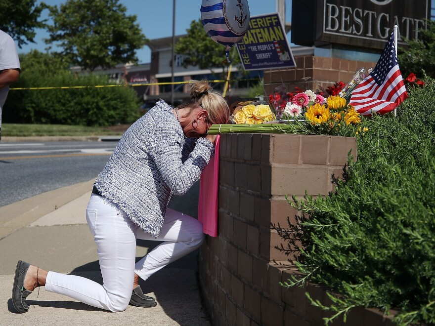 Lynne Griffin pays her respects at a makeshift memorial outside the Capital Gazette offices, one day after a gunman killed five people in its newsroom. Griffin was a journalism student under John McNamara — one of the people killed Thursday.