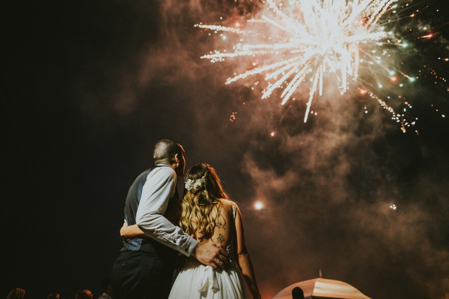 A man and a woman in wedding attire embrace one another. Above them, a firework explodes.