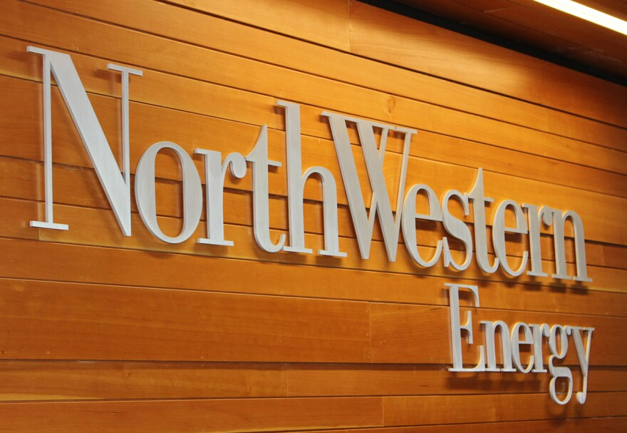 """A sign reading """"NorthWestern Energy"""" in silver type against a tan woodgrain background."""