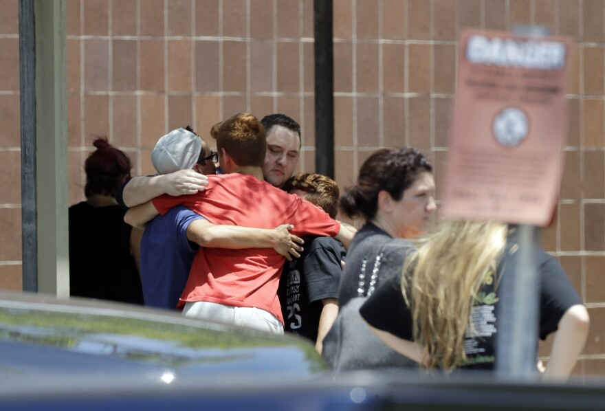 People react outside the unification center at the Alamo Gym, following a shooting at Santa Fe High School Friday, May 18, 2018, in Santa Fe, Texas.