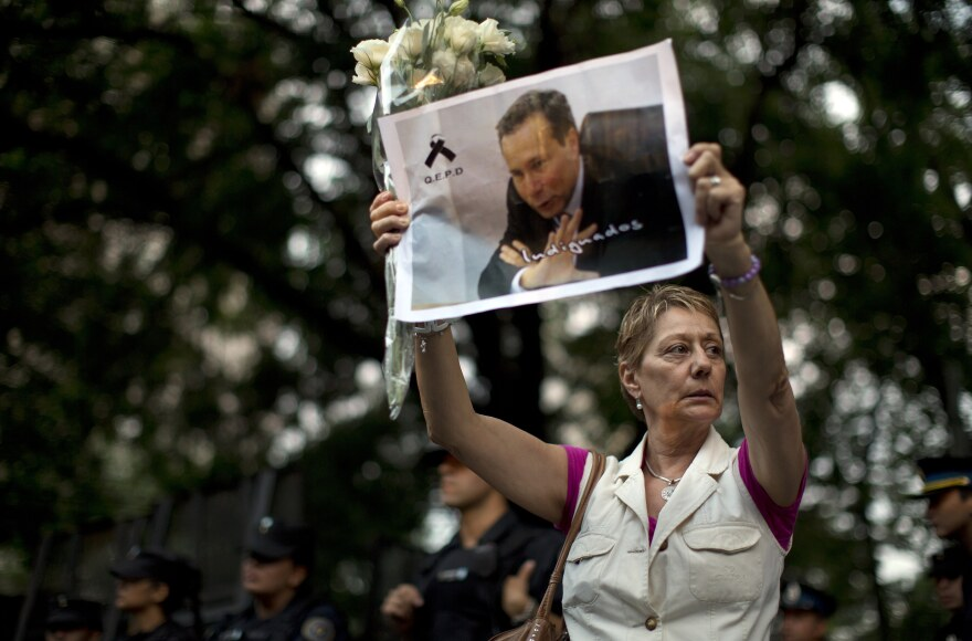 A woman holds up a portrait of late prosecutor Alberto Nisman near the funeral home where a private wake was held for him in January in Buenos Aires.