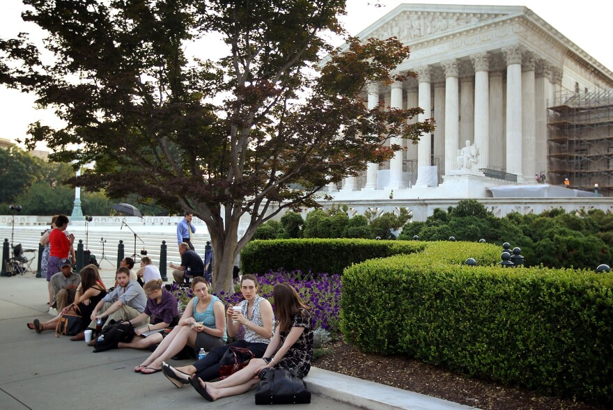 People wait outside the Supreme Court last week for word on the fate of the federal health overhaul law.