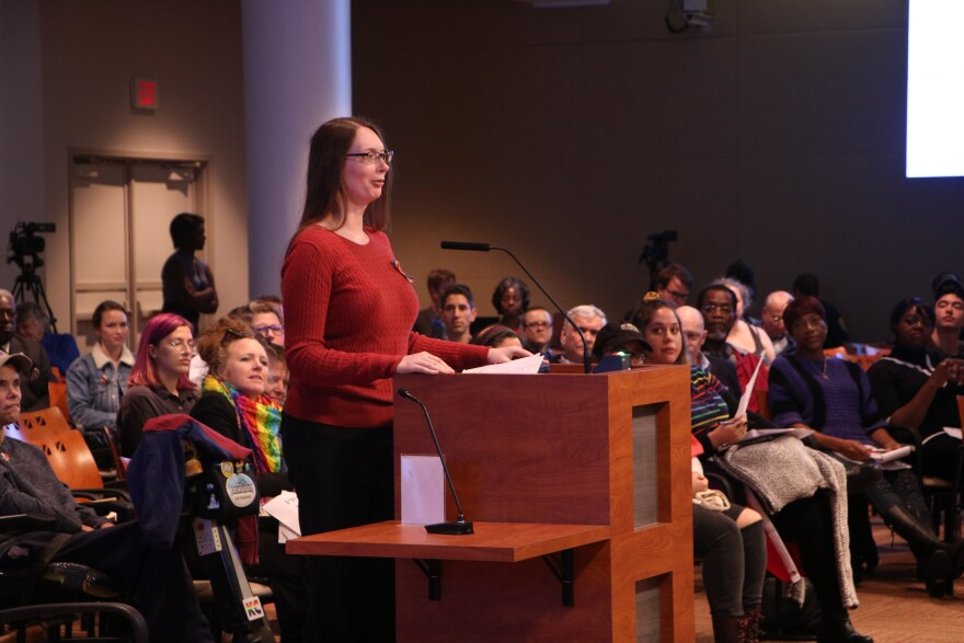 Woman in red shirt and black pants stands at a podium among a crowd of people.