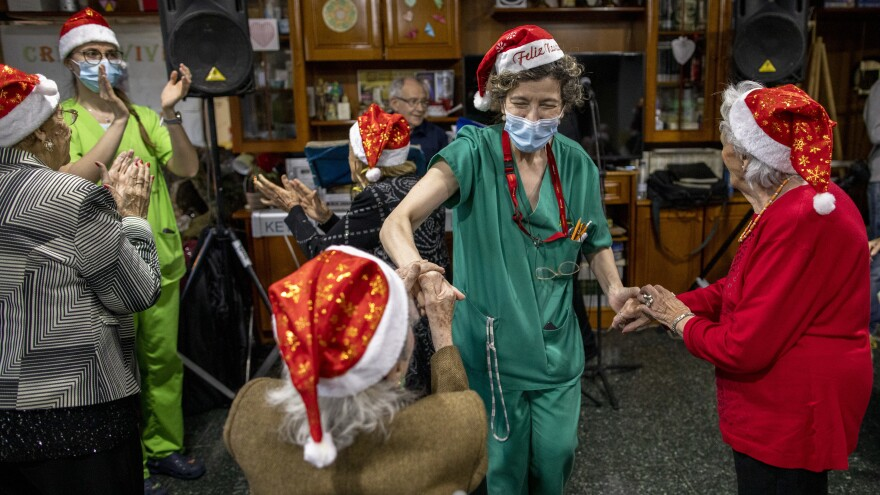 A seniors' residence employee (second right) dances with residents as a band plays on Christmas Eve at Las Praderas home on Dec. 24, 2020, in Pozuelo de Alarcon, near Madrid, Spain. The residence is free of COVID-19 cases.