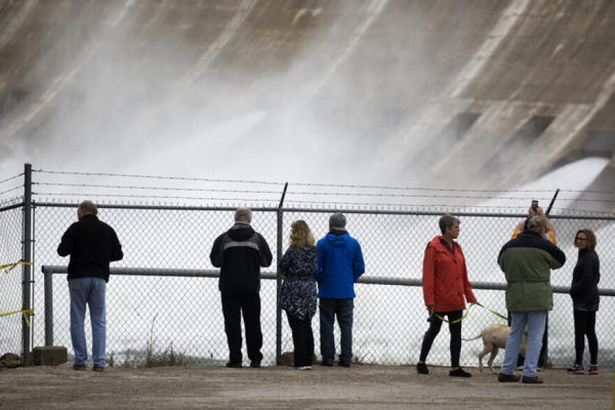 A crowd watches water pour through the Mansfield Dam.
