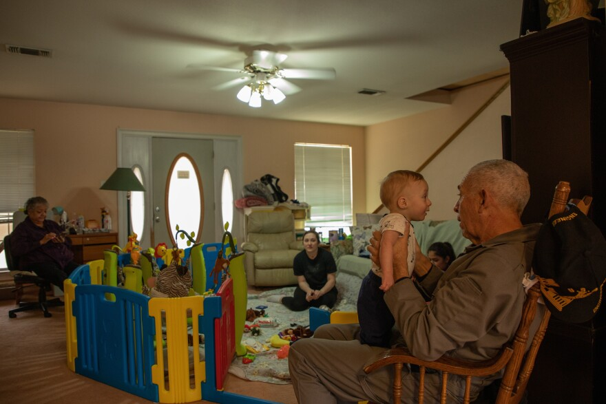 A family sits in a living room cluttered with baby toys.