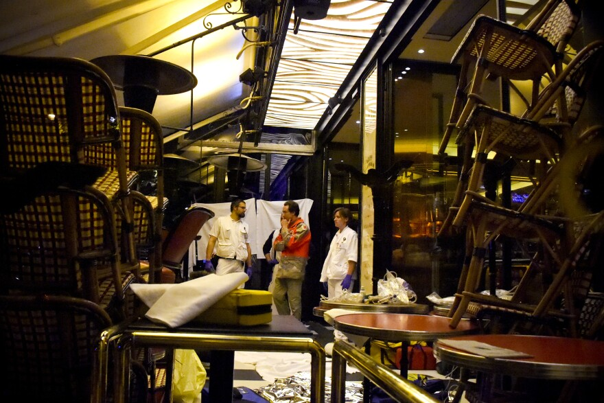 Rescuers stand in a restaurant following an attack in central Paris.