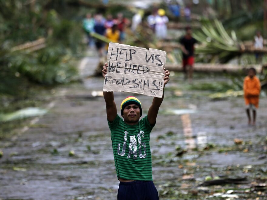 A Filipino typhoon victim pleads for help in the town of Taft, Samar island, Philippines, on Sunday, after Typhoon Hagupit knocked out power and flattened houses there.