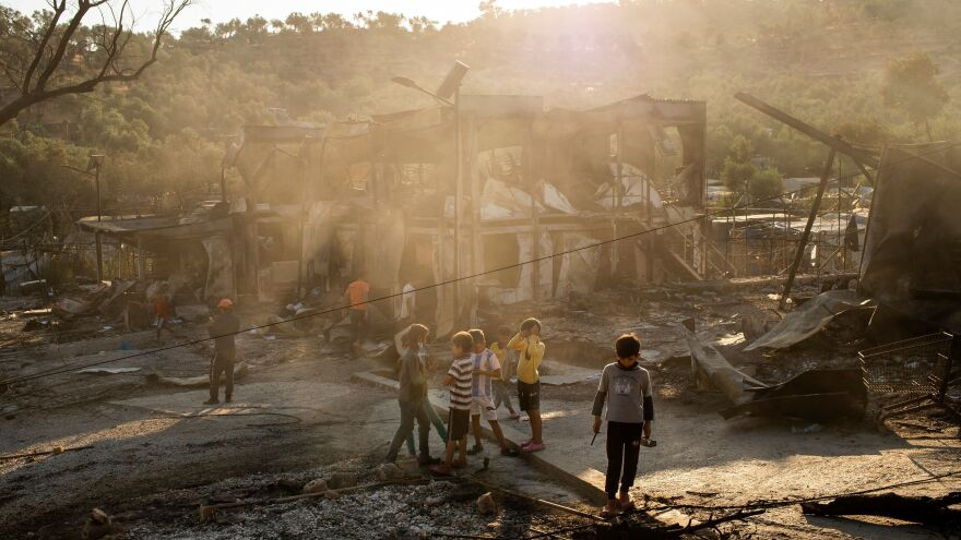 Children walk through the Moria migrant camp on the Greek island of Lesbos after the camp was gutted by fire.