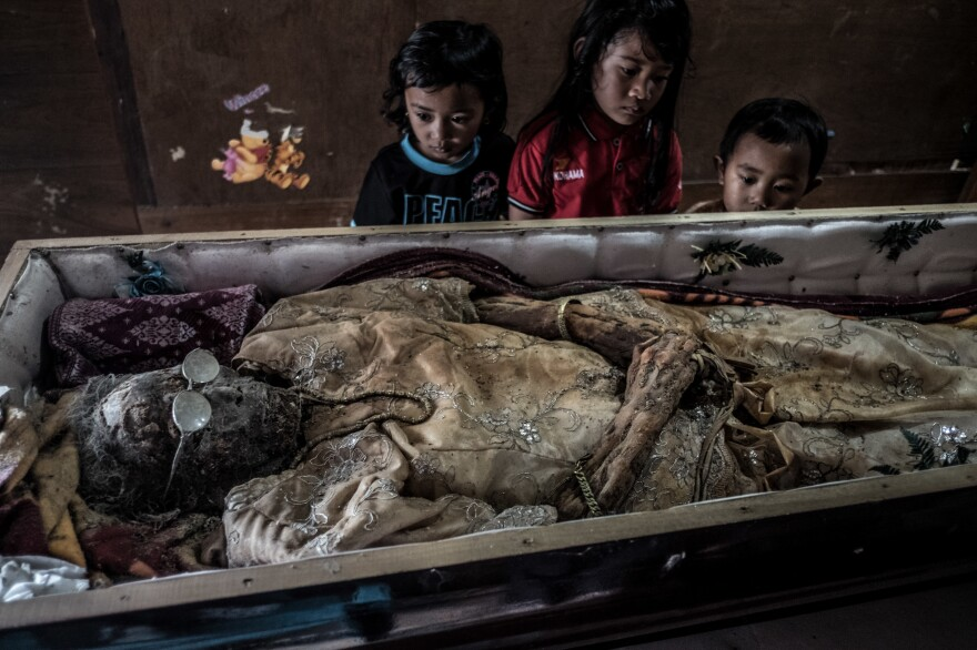 Grandchildren of Alfrida Lantong, who died in 2012, visit her in her coffin at the family's home near Rantepao, a town in the Sulawesi region of Indonesia.