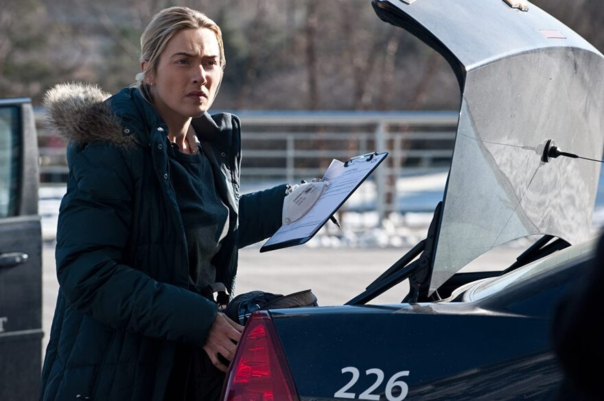 """From the 2011 film """"Contagion"""", Kate Winslet as Dr. Erin Mears standing at the open trunk of her car wearing a winter parka holding a clipboard, pen and protective face mask."""