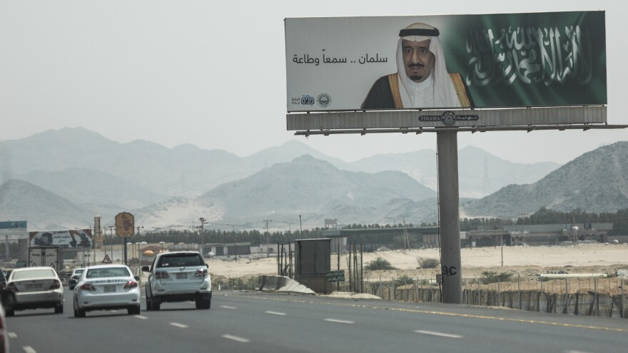 """Cars drive past a banner of Saudi Arabia's King Salman that reads, """"Salman, we hear and obey,"""" near Mecca on Sept. 17. A drop in oil revenue is forcing Saudi Arabia to consider cuts to social programs. The Saudis have declined to cut production, a move that would likely drive up prices, but could also cost the country its current share of the world oil market."""