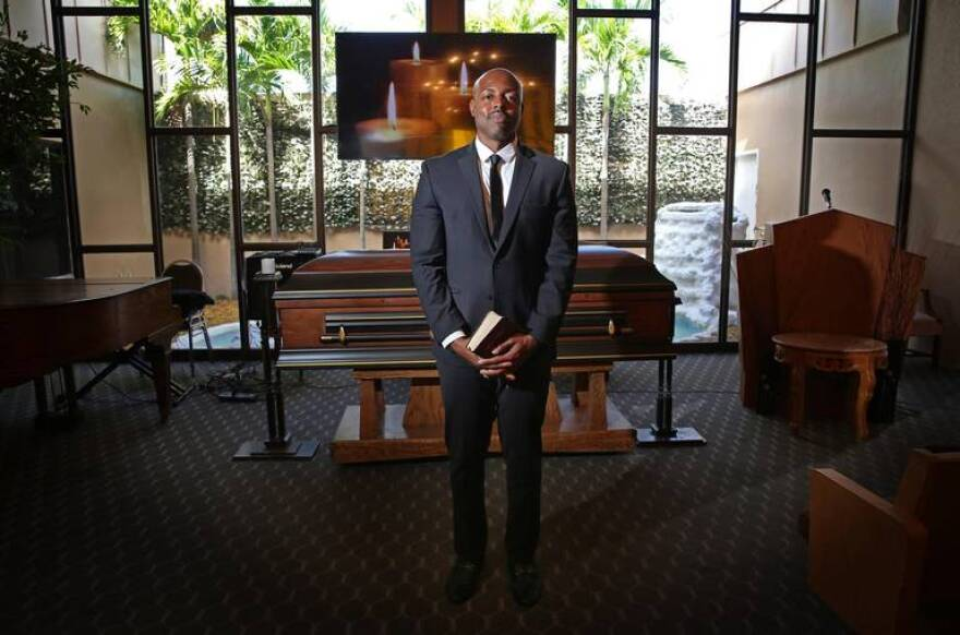 Evans St. Fort in a suit and tie standing in the chapel of his funeral home.