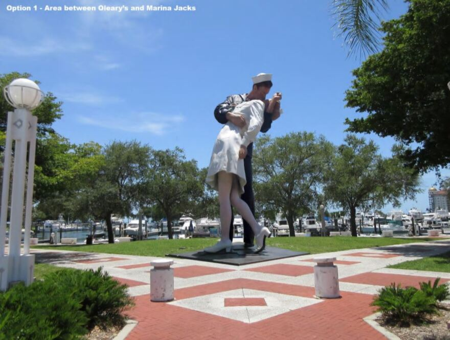 large statue in a park of a sailor kissing a woman