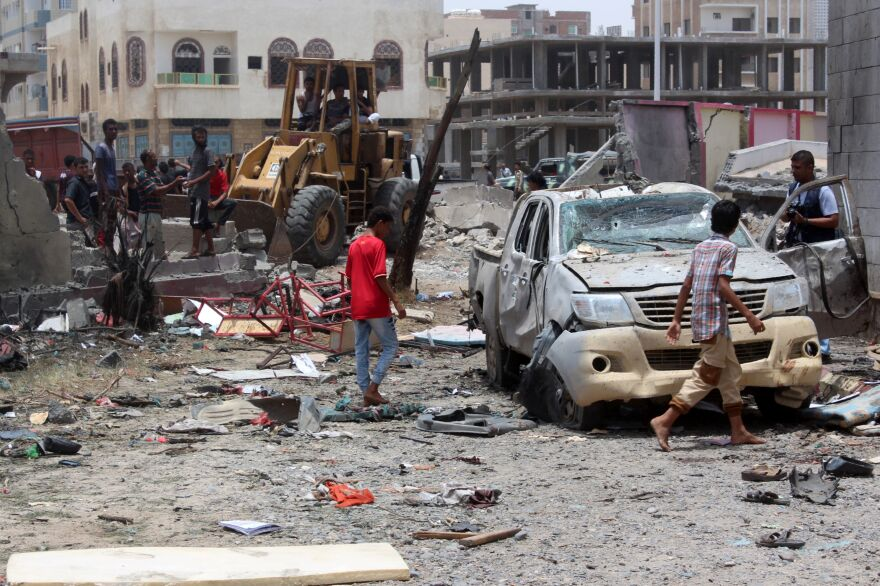 Yemenis inspect the site of a suicide car bombing at an army recruitment center in Aden, Yemen, on Monday.