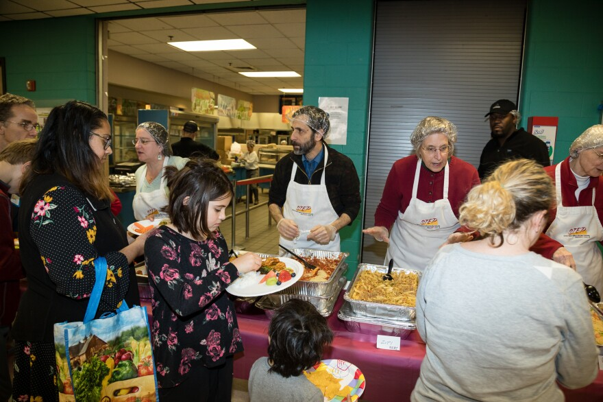 Volunteers hand out food to furloughed workers and their family at a community potluck.