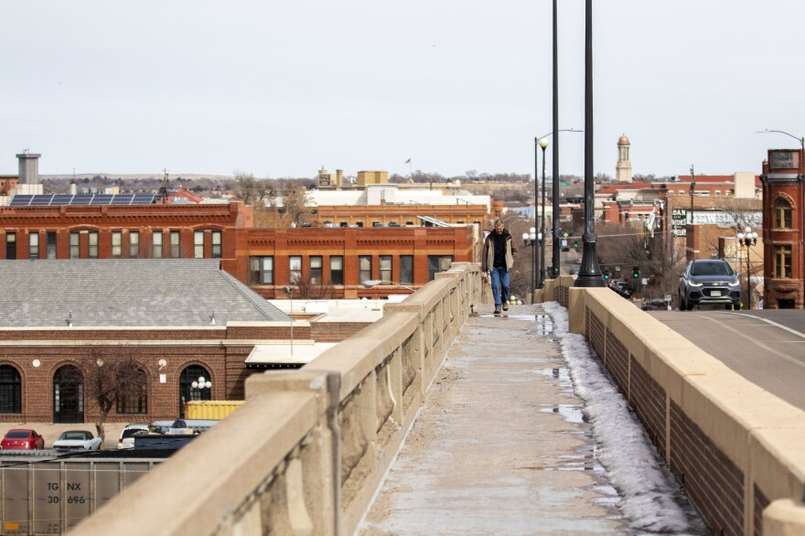 A person walks across a bridge over the Arkansas River in Pueblo. The city is aiming to redefine its economy, and its politics following decades as a solidly blue collar Democratic stronghold.