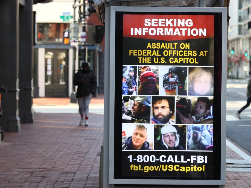 A sign on a bus shelter asks the public for information about people involved in the Jan. 6 Capitol insurrection.