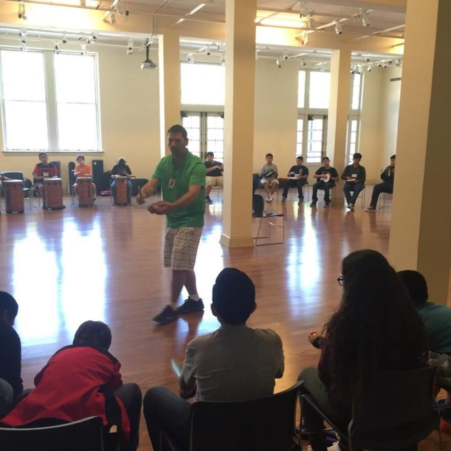 An instructor at the Dallas Winds Band Camp helps students feel the beat.